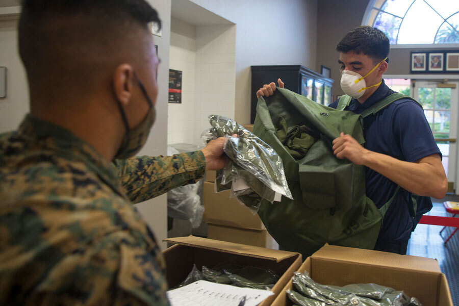 military man passes out personal protective gear