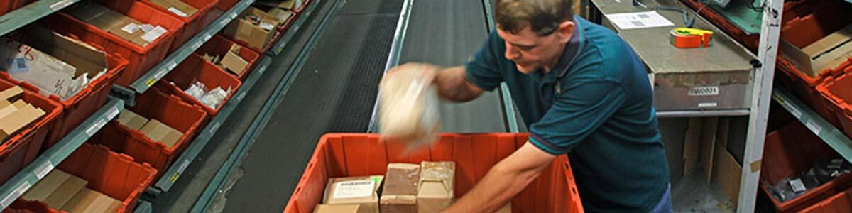 man packages materials in factory
