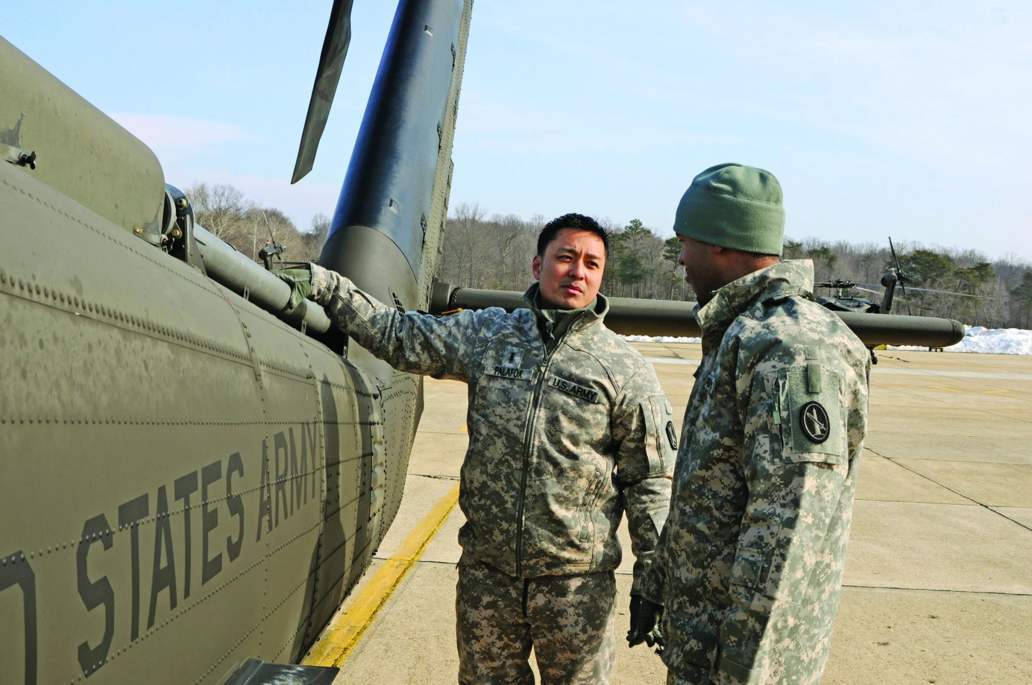 soldiers talk outside helicopter