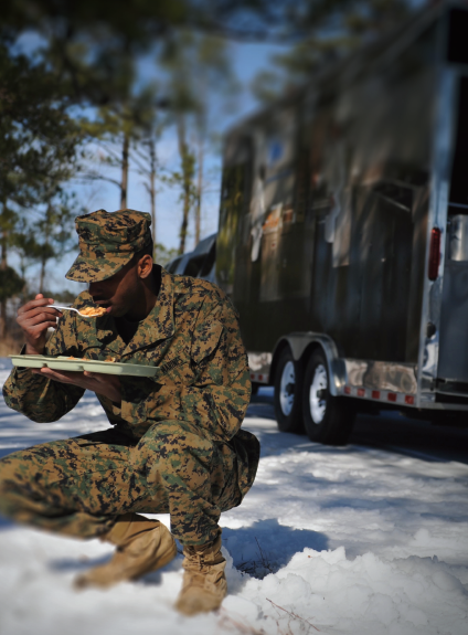 military man eats in snow