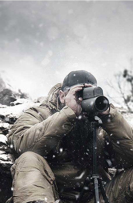 man in snow with scope