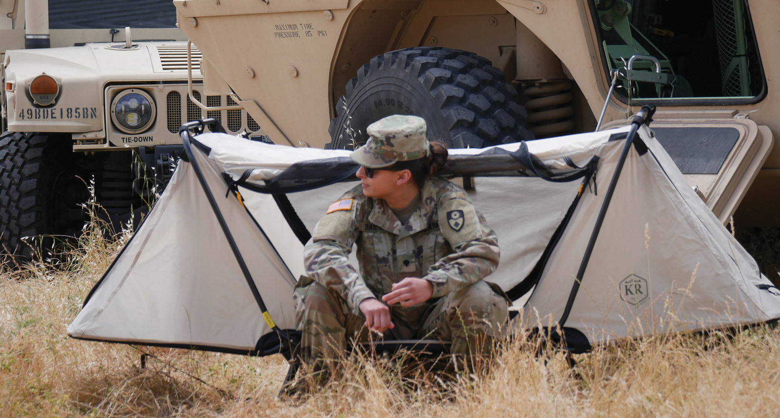 military woman in front of tent